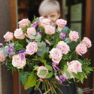 Florystka z Kwiaciarni Internetowej Poczta Kwiatowa trzyma w rękach bukiet różowych róż